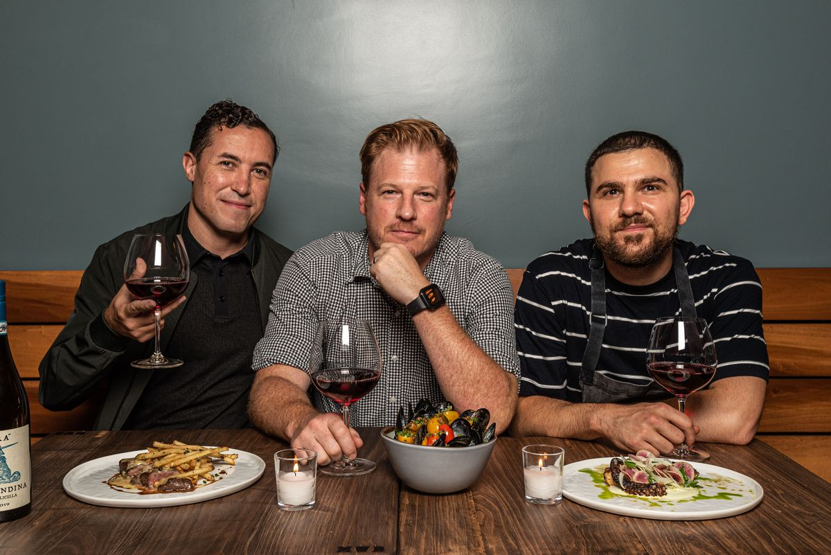 Three people sit facing the camera in front of a table of small plates like steak frites.