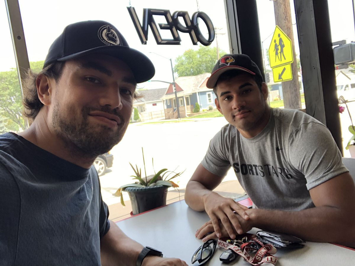 Green Bay teammates Bronson Kaufusi, left, and Christian Uphoff sit at a table in a restaurant.