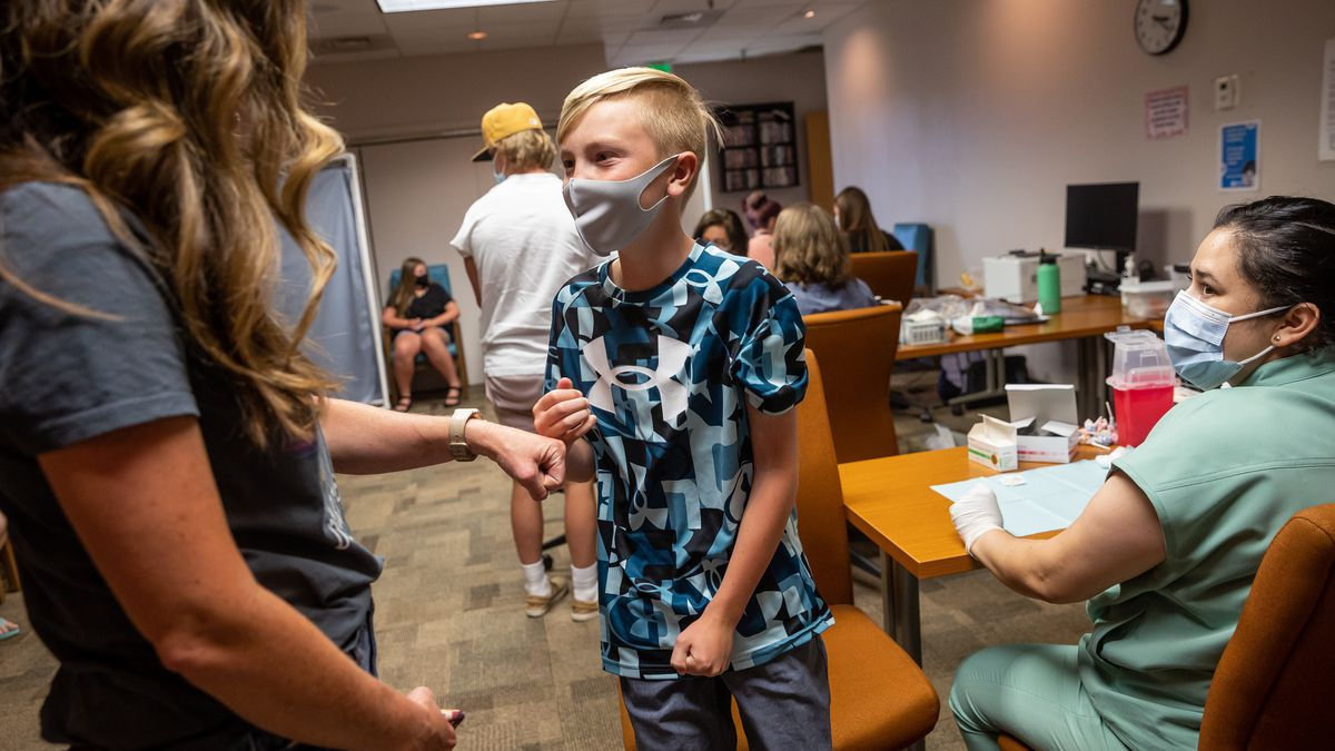 Becky Allen fist-bumps her son, Jack, 12, after he got a shot of the Pfizer-BioNTech COVID-19 vaccine from nurse Estefania Cruz at the Central Davis Senior Activity Center in Kaysville on Tuesday, July 6, 2021.