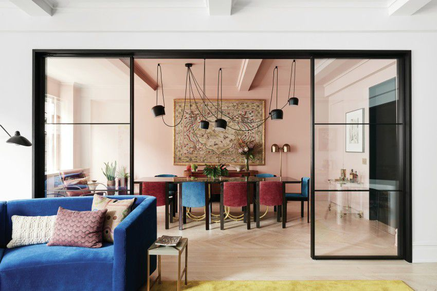 A living room and dining room in a New York City apartment. There is a blue couch, table, chairs, light fixtures, and a glass room divider.