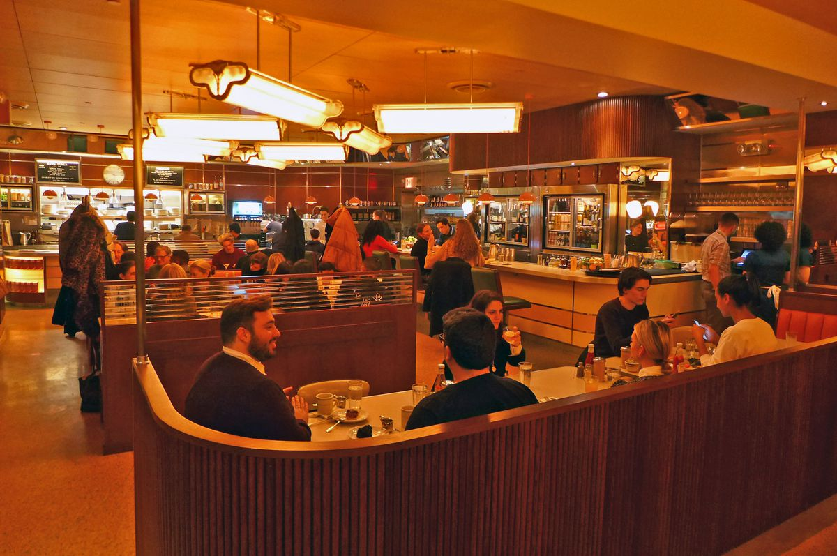 A restaurant interior with curving surfaces and customers sitting at a number of booths.