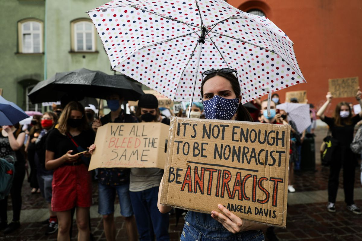 A protester wearing a facemask and holding an umbrella shows...