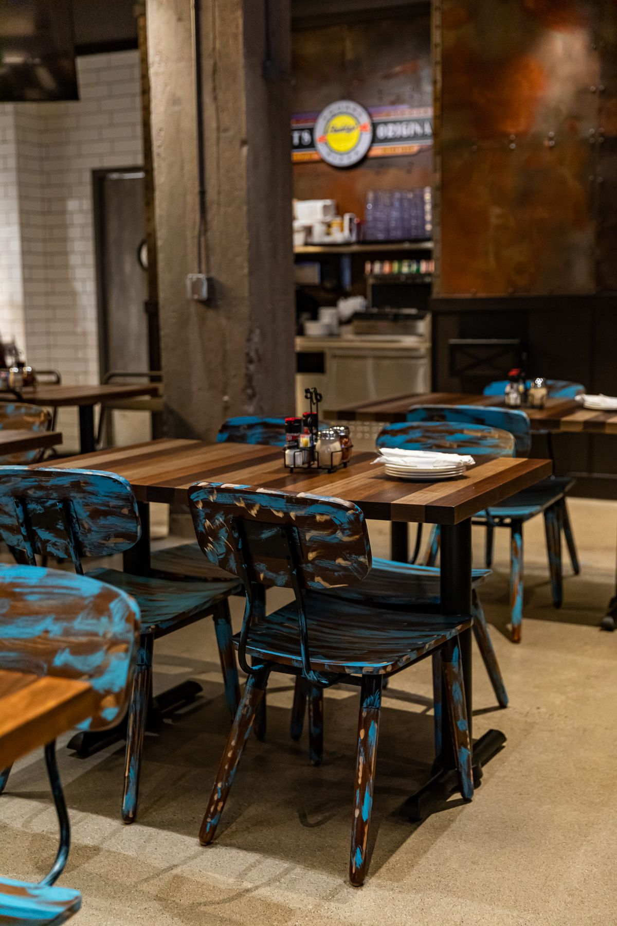 Wildly painted blue schoolhouse chairs at Buddy's Pizza surround striped wood tables.