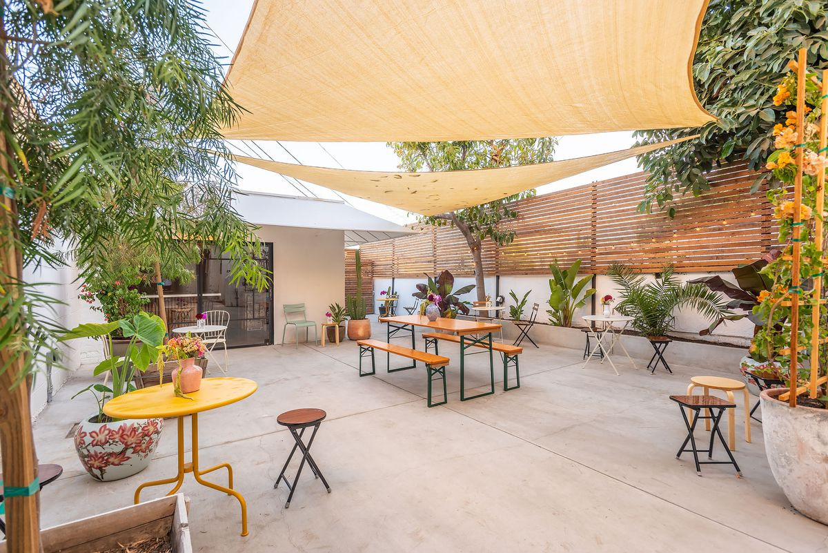 Courtyard dining area of Gamboge with yellow sunshades.