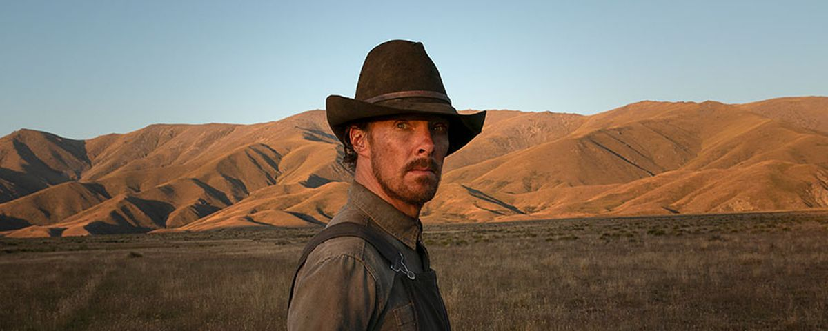 Benedict Cumberbatch in a cowboy hat, standing in a field in The Power of the Dog