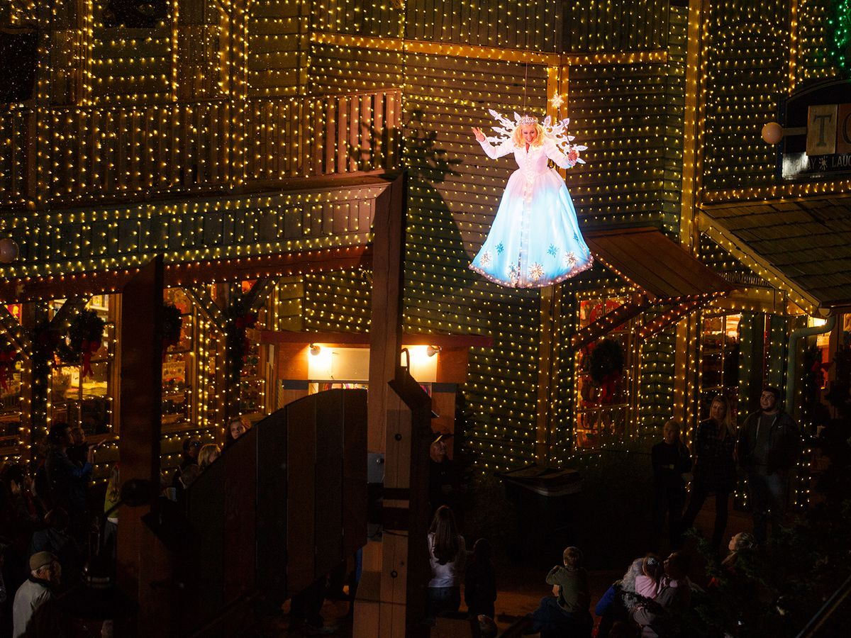 """A woman dressed as the snow angel """"flies"""" above a crowd with lighted buildings in the background."""