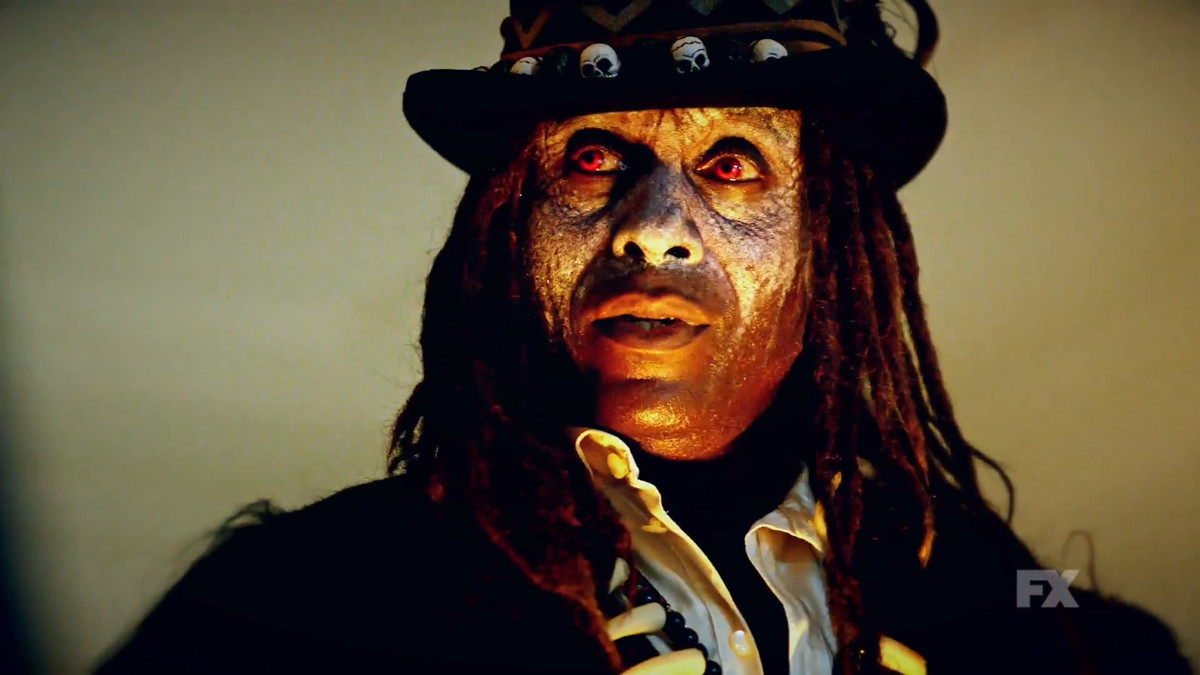 a man with face paint and long dreadlocks, with glowing red eyes, wearing a top hat