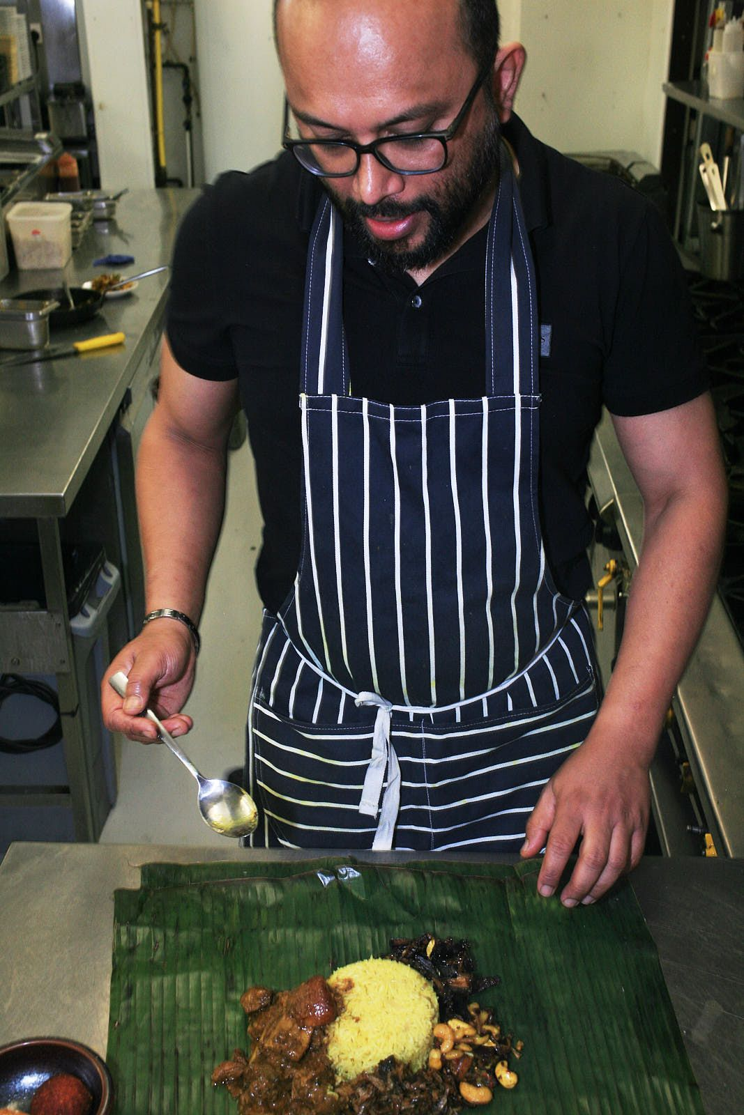 Chef Roshan Ratnayaka, wearing glasses, stands over his lamprais, the Sri Lankan dish of rice, curry, and condiments wrapped in a banana leaf