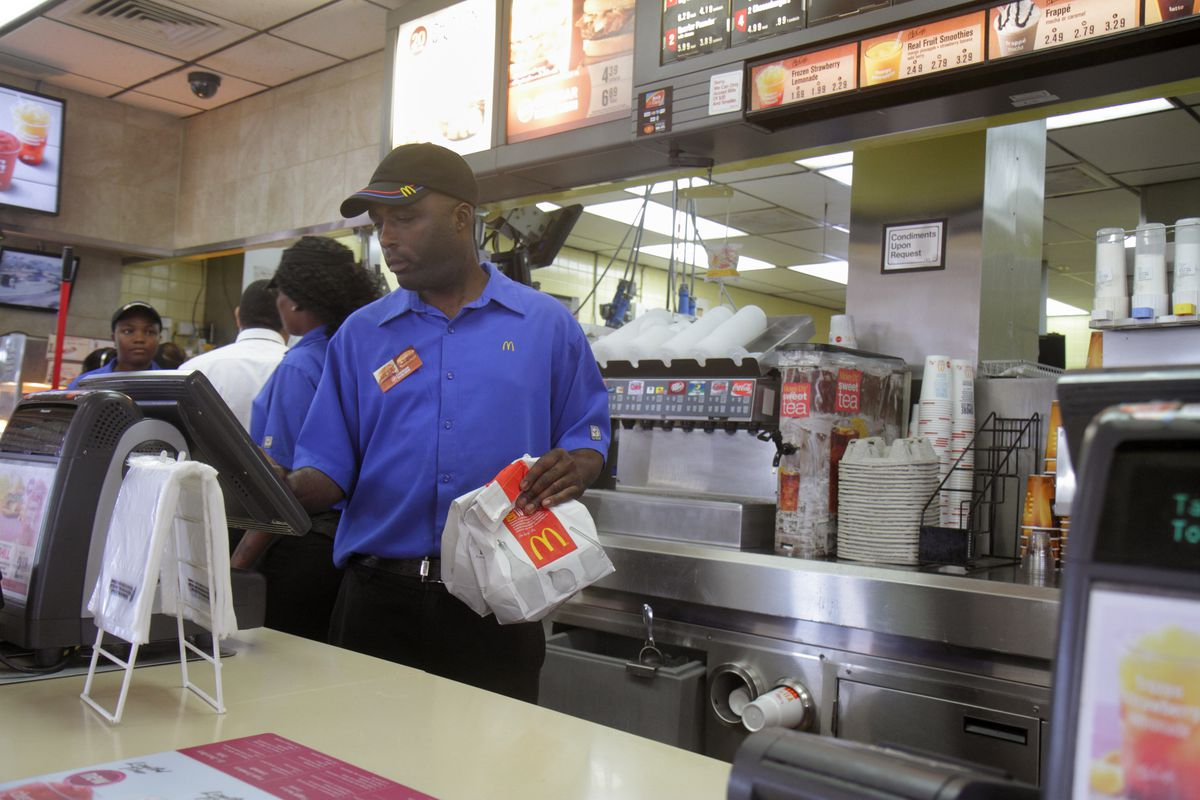 A McDonald's worker behind the counter using a cash register.