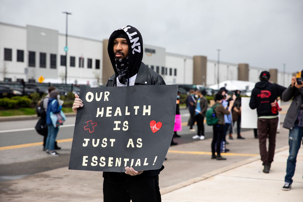 """A protester standing outside an Amazon facility holds a sign that reads """"Our health is just as essential."""""""