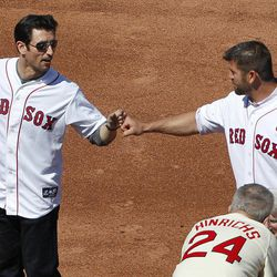 Former Bosotn Red Sox shortstop Nomar Garciaparra, left, greets former catcher Jason Varitek, top right, on the field during ceremonies to celebrate the 100th anniversary of a regular season baseball game at Fenway Park before a game between the New York Yankees and the Red Sox in Boston, Friday, April 20, 2012.
