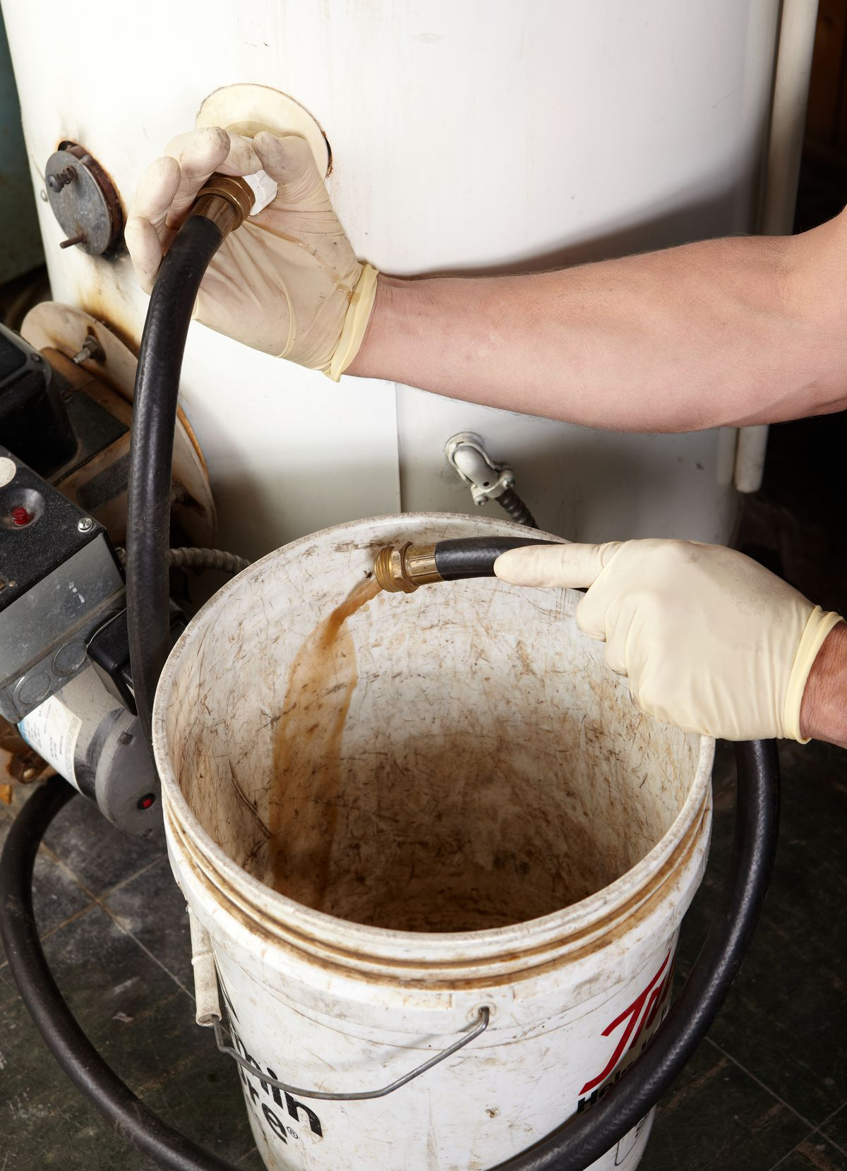 Person Draining Water Heater And Washing Out Sediment