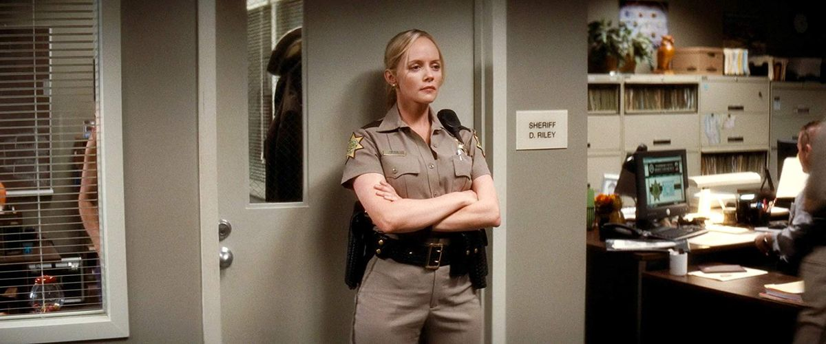judy (marley shelton) wears a police outfit and stands in front of the door of a police station office