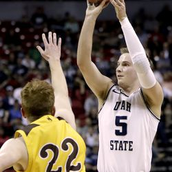Utah State's Sam Merrill (5) shoots as Wyoming's Kenny Foster defends during the first half of an NCAA college basketball game in the Mountain West Conference men's tournament Friday, March 6, 2020, in Las Vegas. (AP Photo)