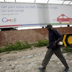 In this photo taken, Monday, Sept.17, 2012. An unidentified man walk past a Google advert in Lagos, Nigeria. With all its cutting-edge technology, Google Inc. has turned back to the text message in its efforts to break into Nigeria's booming economy. The search engine has started a service in Nigeria, as well as Ghana and Kenya, allowing mobile phone users to access emails through text messaging. That comes as the company's office in Lagos has begun working with small business owners in this nation of more than 160 million people.