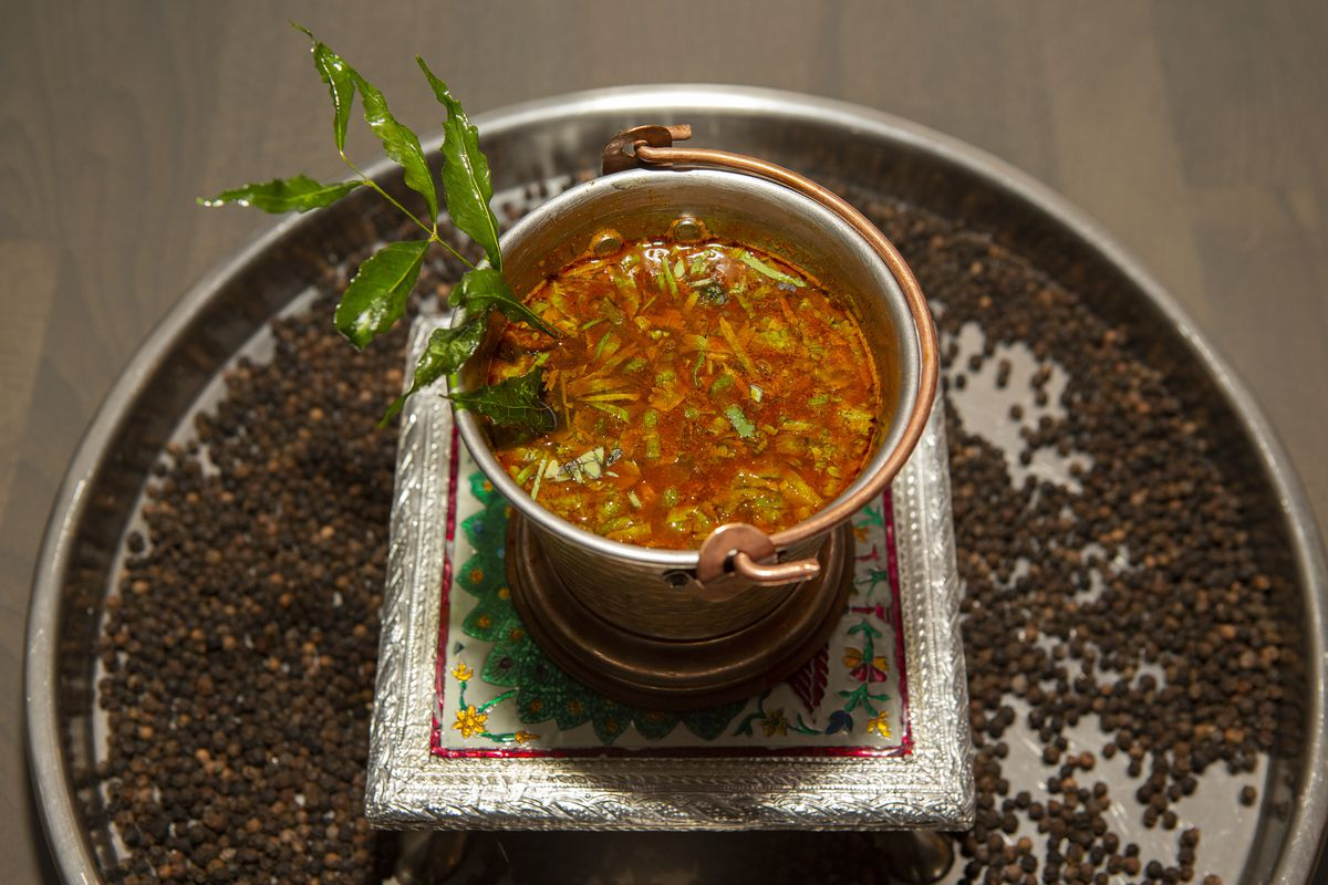 """""""Soup"""" in a bowl with curry leaves."""