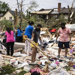 Dozens of volunteers help clean up a demolished home on Princeton Circle near Ranchview Drive in Naperville after a tornado ripped through the western suburbs overnight, Monday afternoon, June 21, 2021.