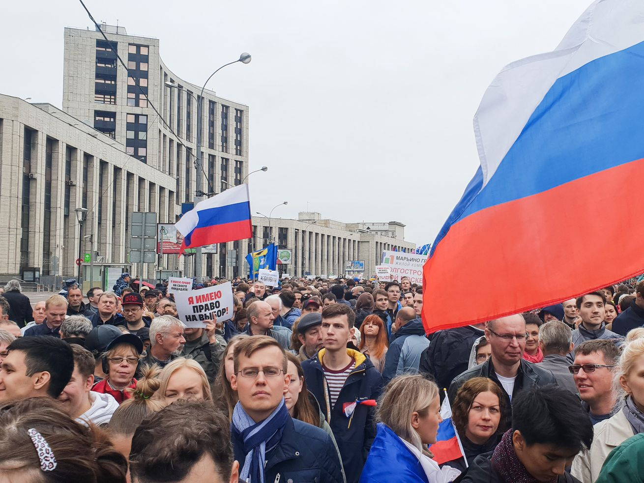 A crowd fills a street in Moscow as people carry flags in protest.