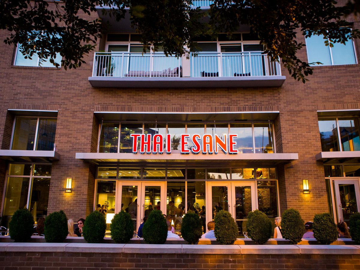 exterior shot of the restaurant, a brick building, and Thai Esane sign in large red capital letters