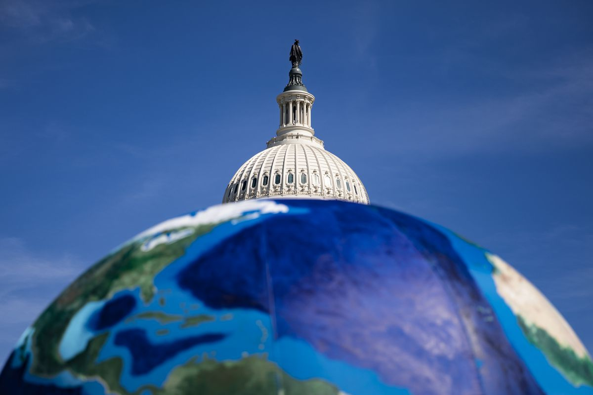A large model of the Earth with the top of the US Capitol building in the background.