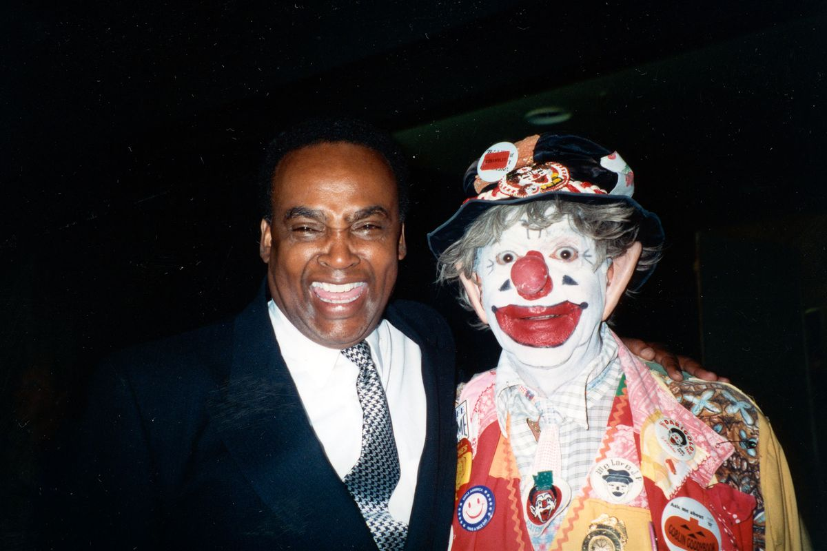 A man in a black suit, white shirt, and gray tie (left) poses with a big smile next to a man (right) dressed as a clown, with a red and yellow jacket full of buttons and a crumpled hat, plus white and red clown makeup and a gray wig.