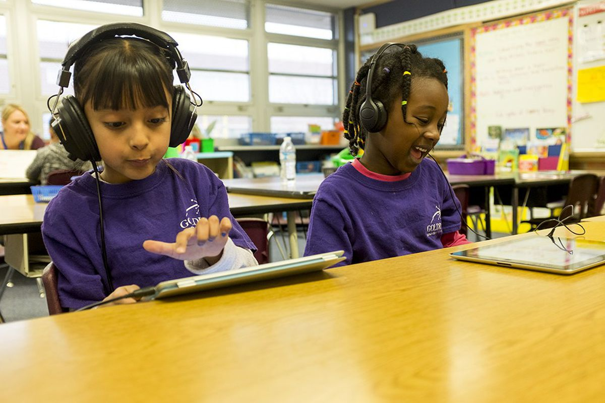 Two first-grade children in purple shirts and wearing headphones work on iPads in a classroom.