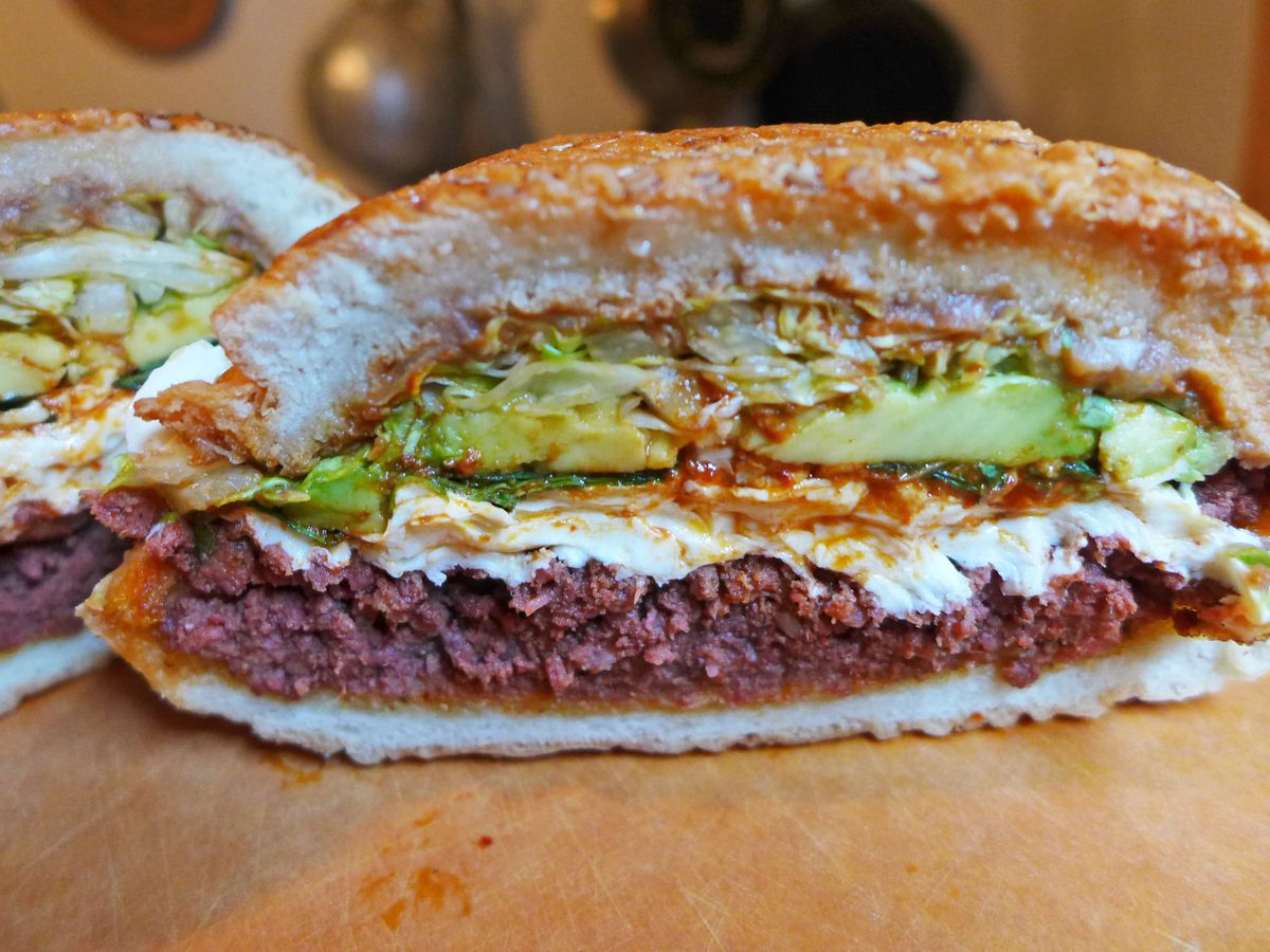 A round sandwich with avocado, string cheese, and skinless sausage.