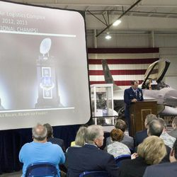 """Maj. Gen. Brent Baker Sr. jokingly awards the Ogden Air Logistics Complex the """"national championship"""" of air logistics during a change of command ceremony at Hill Aerospace Museum, Monday, Sept. 8, 2014. Brig. Gen. Carl A. Buhler assumed command of the Ogden Air Logistics Complex from Baker."""