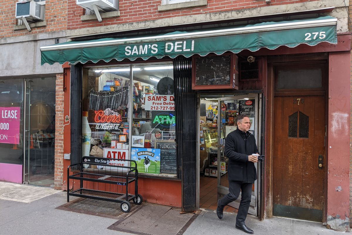 A bodega with a green awning as a well dressed man emerges.