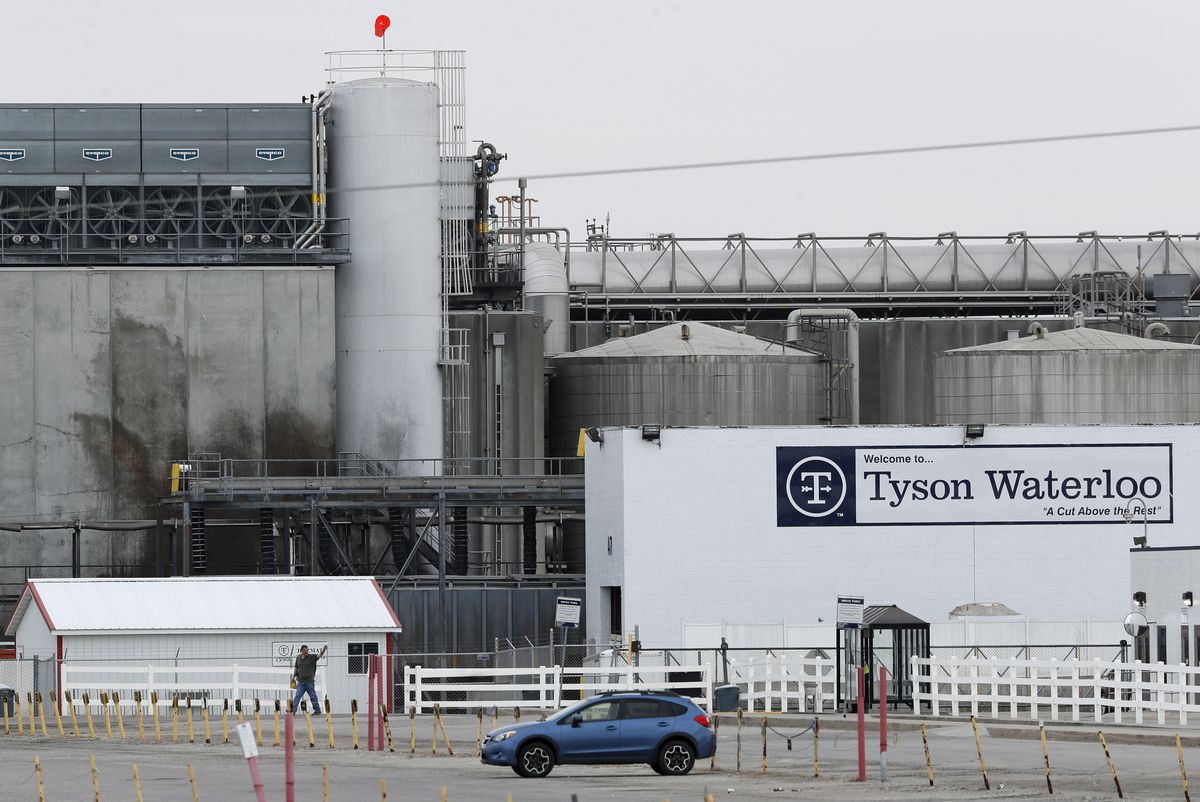 The exterior of a Tyson Foods plant, with one car and one person in the foreground.
