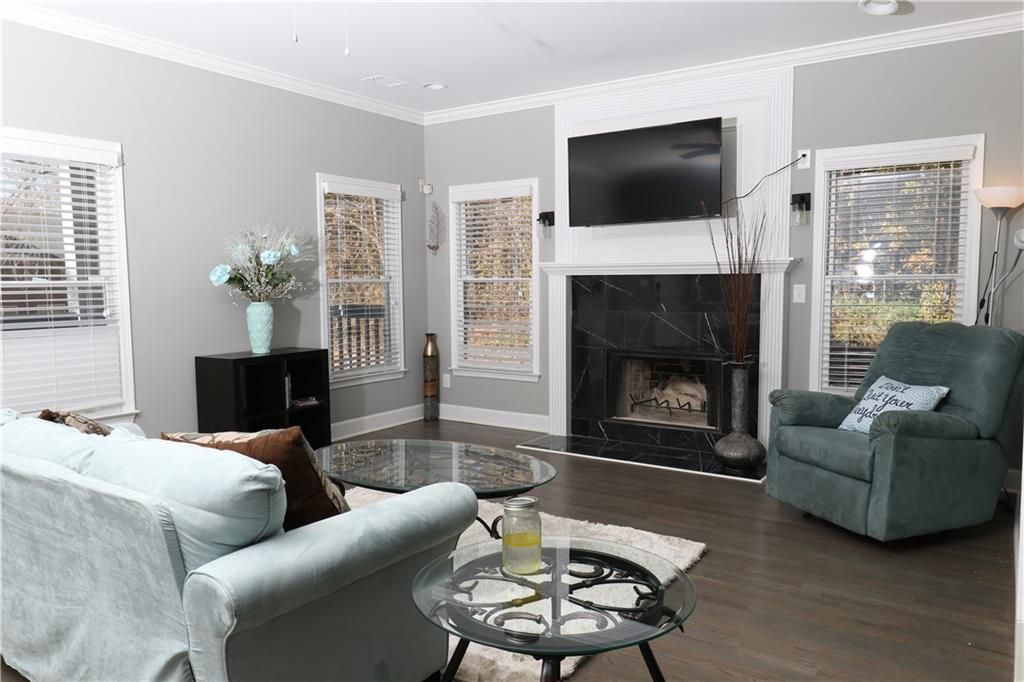 Living area with black fireplace, couch, chair, coffee table, end table and area rug.