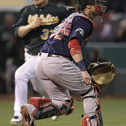 Oakland Athletics' Brandon Moss, left, runs to score as Boston Red Sox catcher Jarrod Saltalamacchia waits for the ball  in the second inning of a baseball game Friday, Aug. 31, 2012, in Oakland, Calif. Moss scored on a single by A's Jonny Gomes.
