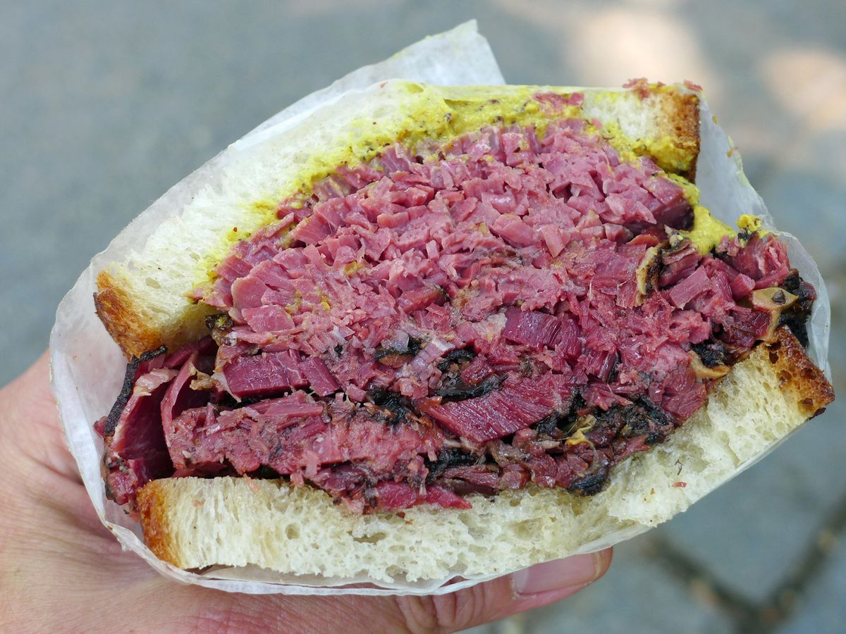 Half of a pastrami sandwich on rye with mustard