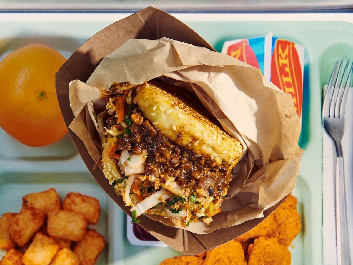 A mushroom-based sloppy Joe sits in a brown plastic wrapper above a lunch tray.