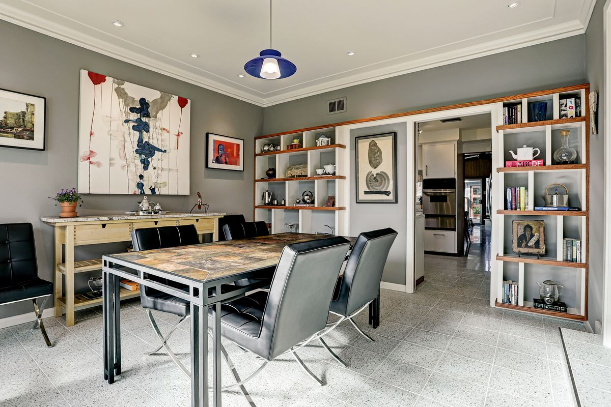 A dining room has a four-person table, terrazzo floors, and built-in open shelving along one wall.