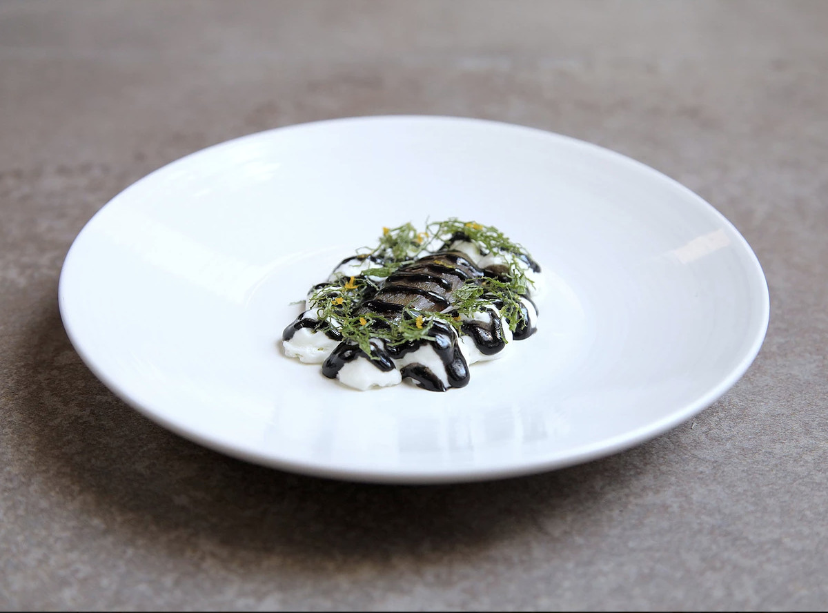 A dish consisting of black and white sauces topped with green herbs