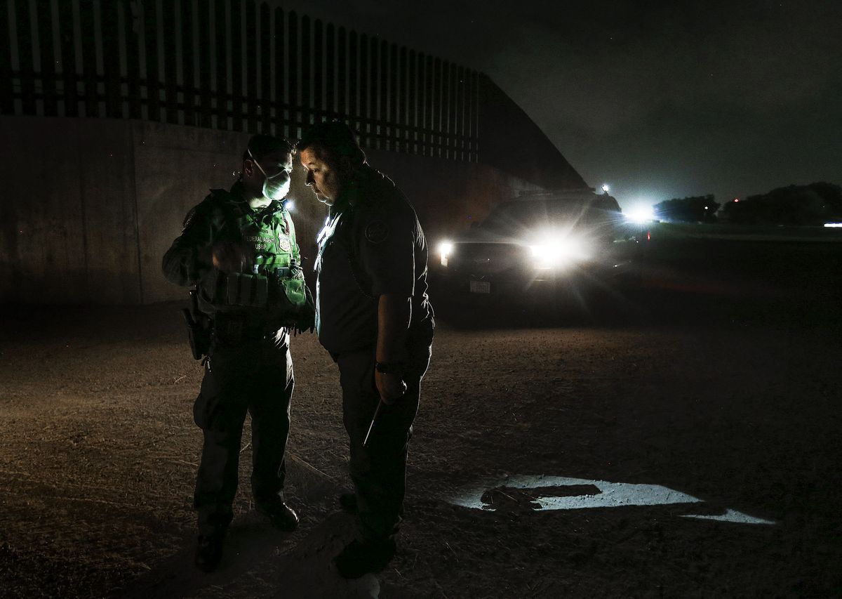 Border Patrol agents Jesse Moreno, left, and Robert Hess confer after finding a group of undocumented migrants, mostly women and children, seeking asylum in McAllen, Texas, on Tuesday, June 22, 2021.