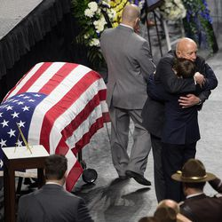Lane Larkin hugs Jack Barney at funeral services for Jack's dad, Unified Police officer Doug Barney, at the Maverik Center in West Valley City on Monday, Jan. 25, 2016.