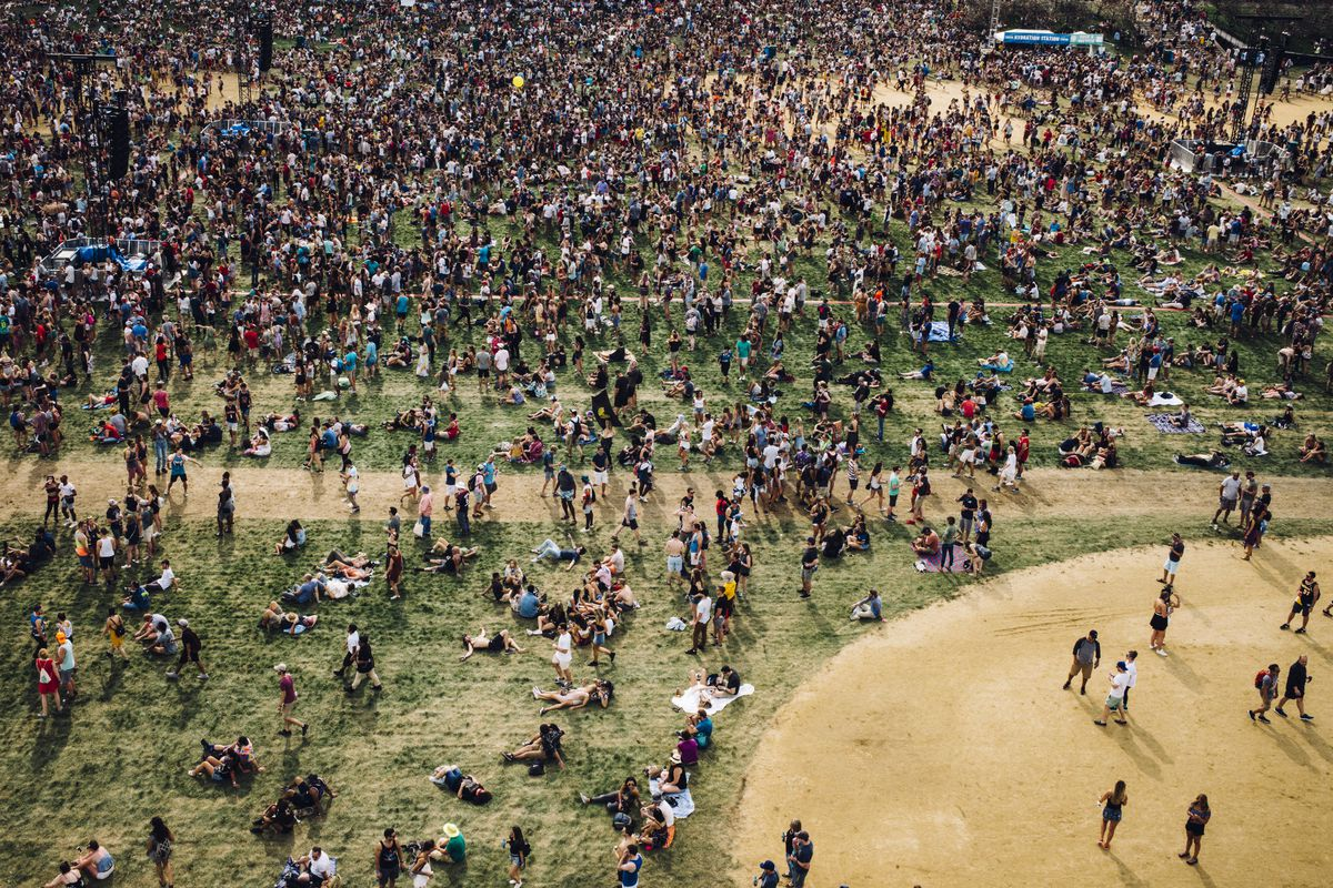 An aerial view of a massive crowd at Lollapalooza in Grant Park. There's grass and part of a sandy baseball field.