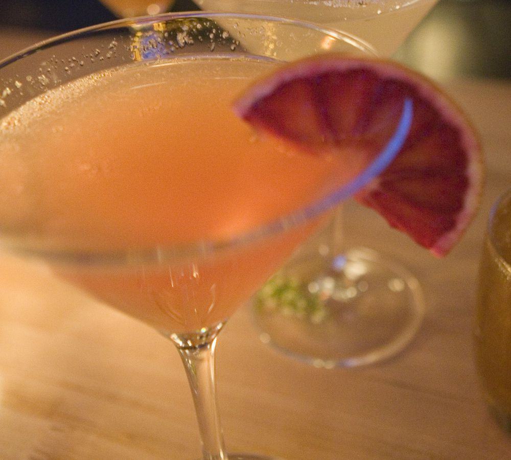 A closeup of a peach-colored cocktail in a martini glass garnished with grapefruit.