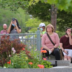 Onlookers gather to watch the Angel Moroni statue being removed from the Salt Lake City Temple of The Church of Jesus Christ of Latter-day Saints by workers from Jacobsen Construction on Monday, May 18, 2020.