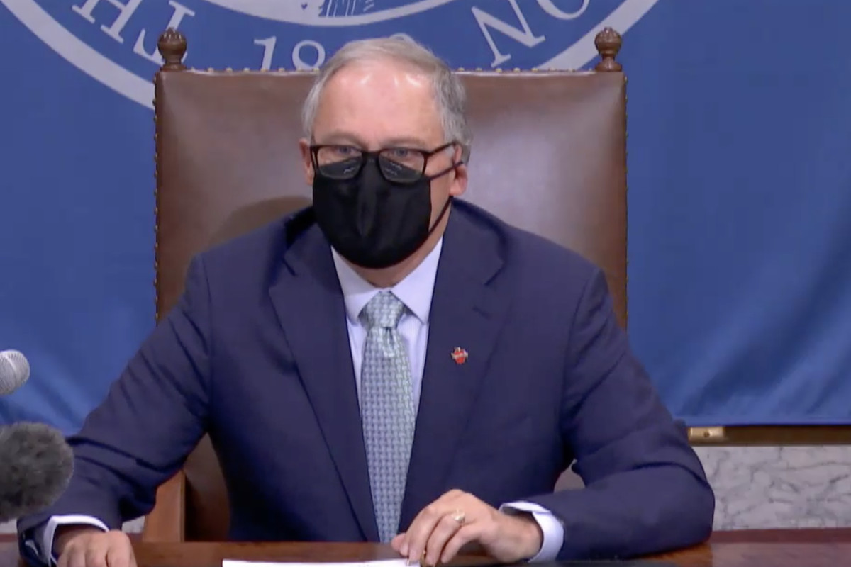 Washington Gov. Jay Inslee sits in a leather chair behind a desk, wearing a face mask