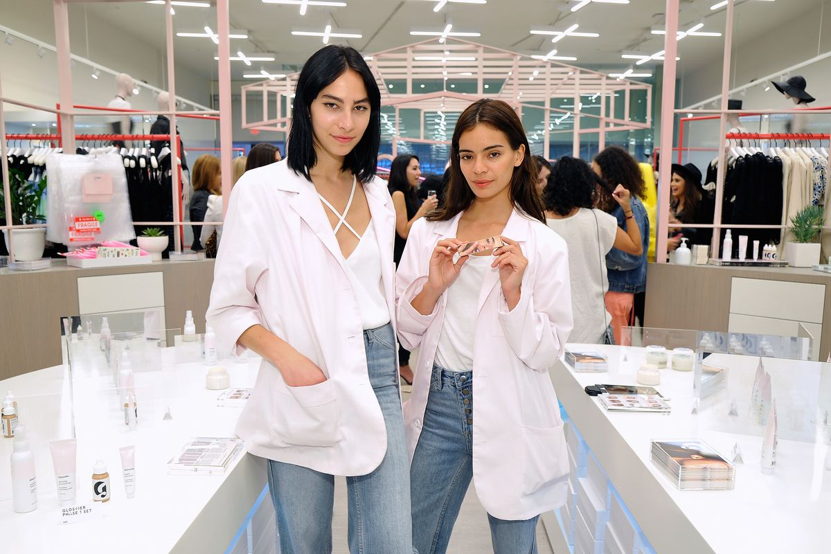 Two women standing in a Glossier pop-up shop at Nasty Gal Santa Monica