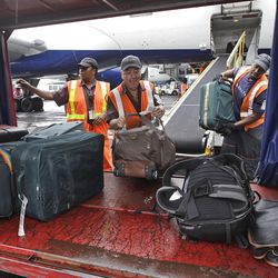 Delta Air Lines ramp agents unload bags at JFK International airport in New York. U.S. airlines collected more than $1.7 billion in baggage fees during the first half of the year.