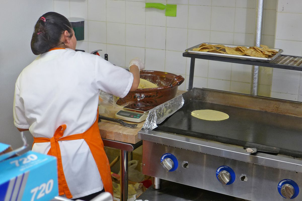 A woman seen from behind pulls masa from a metal bowl to make tortillas.