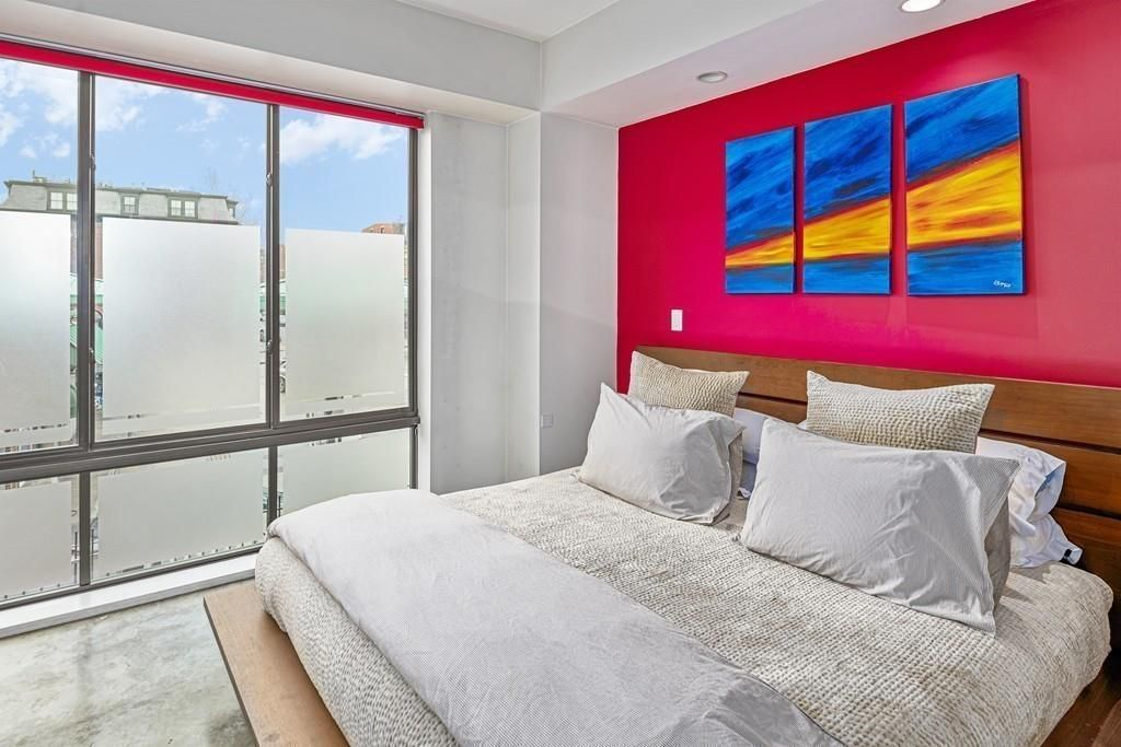 A bedroom with a bed and a bank of windows.