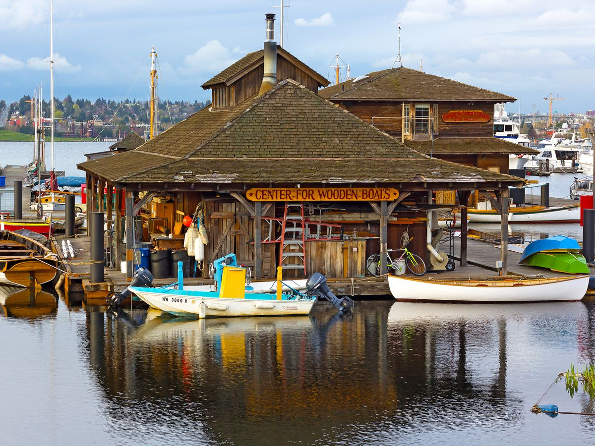 A wooden building with a hip roof on a pier surrounded by boats, including canoes and rowboats.