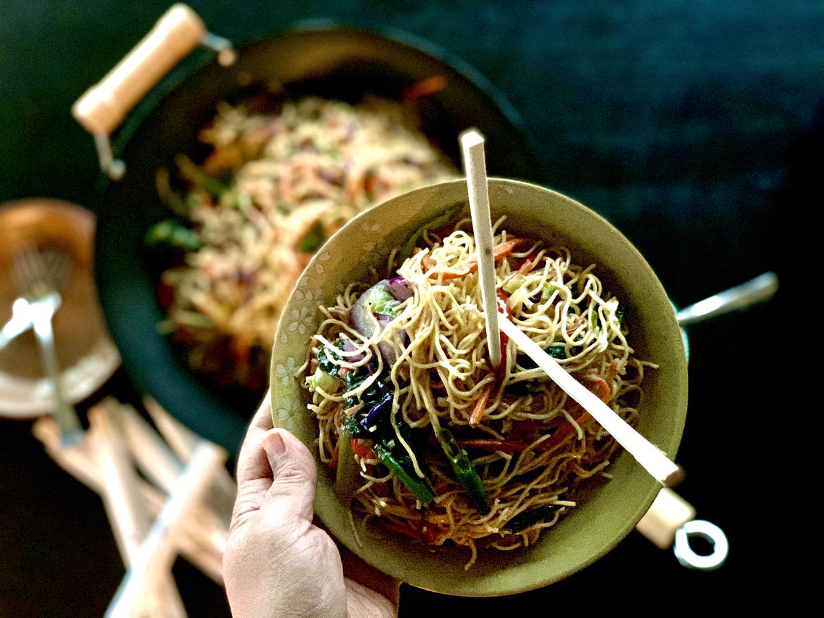 A bowl full of thin noodles and veggies, held up with a hand.