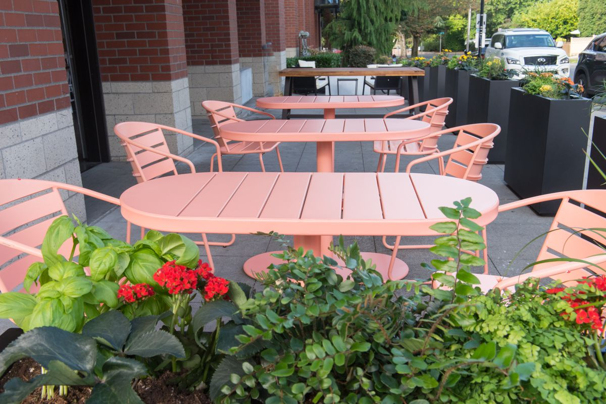 A view of the patio at Eden Hill Provisions, with light pink tables and chairs.