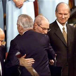 President James E. Faust hugs Elder Neal A. Maxwell at the end of a general conference session. Elder David B. Haight and Elder Russell M. Nelson look on.